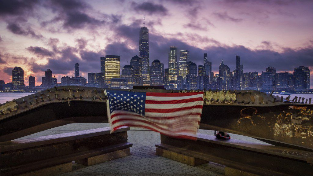 A picture of the American flag in front of the New York City skyline